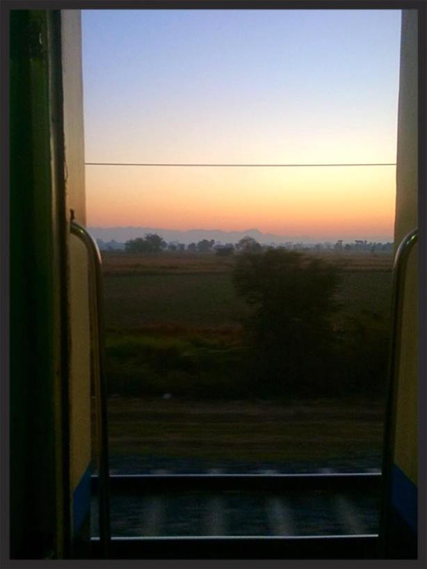 View from the Overnight Express Train - the carriage doors are kept open for the entire journey - in the distance the Burma jungle and forest can be seen