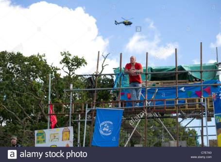 dale-farm-eviction-male-on-scaffold-tower-above-barricaded-entry-to-C7E7A3